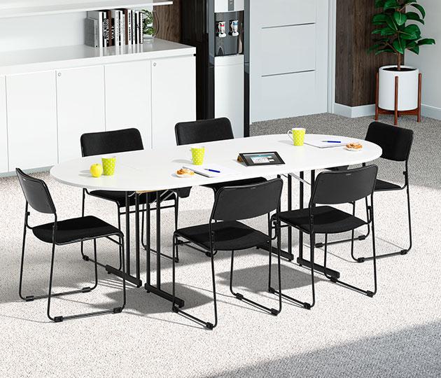 konferensbord med vit skiva och svart stativ och svarta stolar.